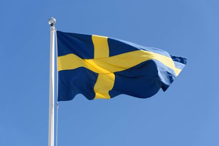 Flag of Sweden waving on a clear blue sky background in close-up (high details) Imagens