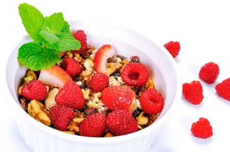 Bowl of homemade organic granola with oats, nuts, raspberries and strawberries decorated with leaves of mint in close-up