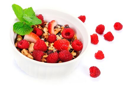 Bowl of homemade organic granola with oats, nuts, raspberries and strawberries decorated with leaves of mint on a white background