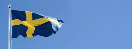 Wide advertisement banner of Sweden flag waving on a clear blue sky background in close-up with copy space.