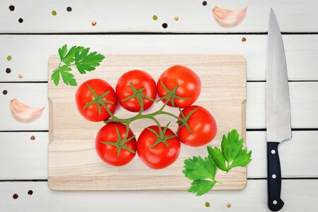 Top view of red fresh tomatoes with green leaves on a wooden board with aromatic spices. Imagens