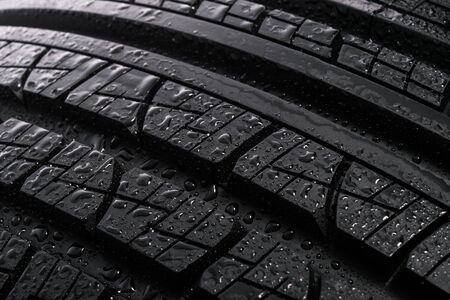 Surface of a new and modern multi season car tyre with water drops. Studio shot (high details) Stock Photo