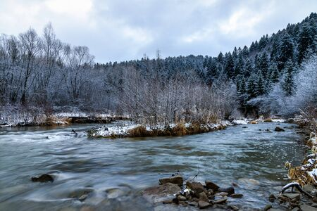 December nature scenery landscape - picturesque river among mountains and frosted trees at daybreak (HDR photo merge)