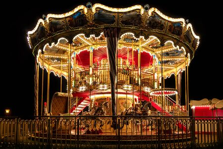 Illuminated classical carousel at night on a street of Gdansk city