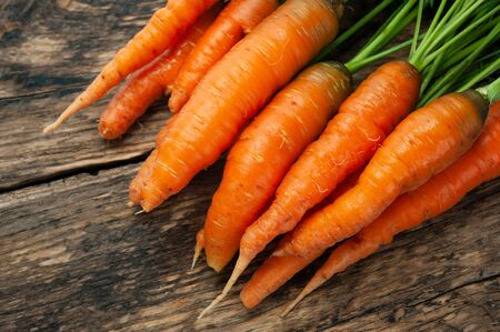 Bunch of fresh organic carrots on a wooden rustic table.