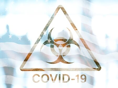 COVID-19 triangle biohazard warning sign on a blurred background of the group of people and American flag