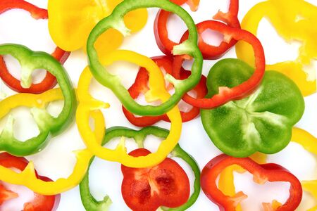 Full frame abstract vegetables background - top view of multicolored sliced peppers on a white background