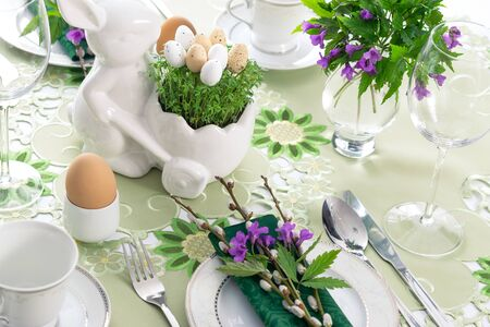 Elegant Easter holiday table settings decoration with fresh early spring violet flowers, cress leaves and eggs. Stock Photo