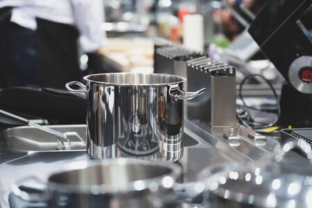Interior view of a professional kitchen in a restaurant or hotel with selective focus on stainless steel pots