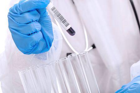 Docteur en vêtements de travail de protection testant le tube d'échantillon de sang dans le laboratoire médical en gros plan
