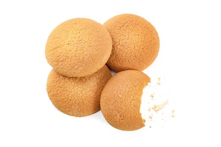 Cookies policy concept - heap of whole biscuits and one bitten with crumbs isolated on a white background