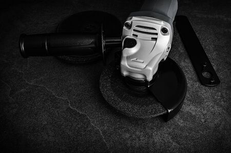 Low Key view of an angle grinder on concrete floor with accessories