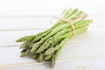 Bunch of fresh raw asparagus tied with a burlap twine on a wooden rustic table