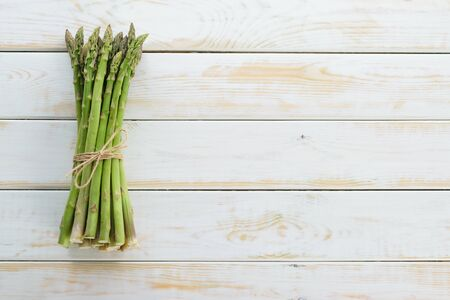 Top view of bunch of fresh raw asparagus tied with a burlap twine on a wooden rustic table (copy space)