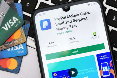Krakow, Poland - September 30, 2020:  PayPal application  in Google Play store next to Visa and Mastercard cards. PayPal is an online electronic finance payment system. Editorial