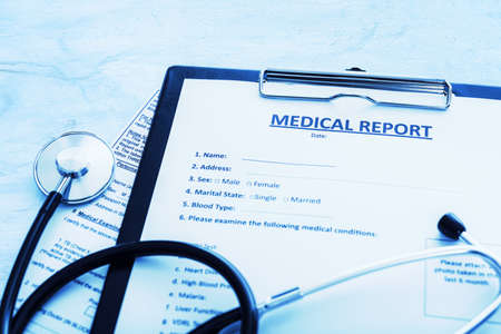 Patient treatment concept - medical report documents with pen and stethoscope in close-up (blue toned image)