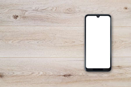 Top view of a new modern black frameless smartphone mockup with blank white screen on a wooden table (copy space).