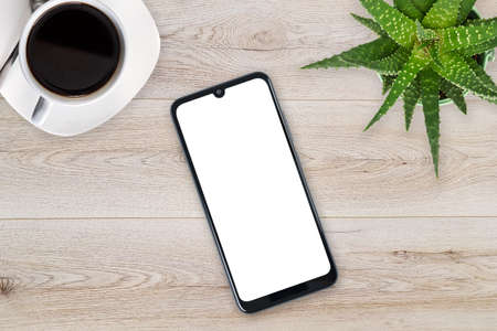 Top view of a new modern smartphone mockup with blank white screen on a wooden table with coffee and green flower (copy space).