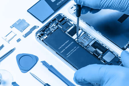 Professional occupation services concept - technician or engineer is repairing modern smartphone motherboard in the professional laboratory (blue toned) Standard-Bild