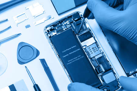 Professional occupation services concept - technician or engineer is repairing modern smartphone motherboard in the professional laboratory (blue toned)
