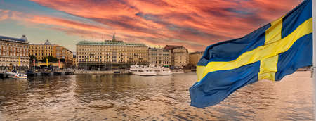 Golden hour panorama of historical Stockholm waterfront at sunset with national flag of Sweden on the first ground. Standard-Bild