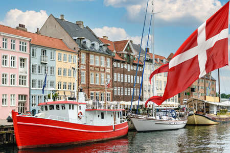 Nyhavn a 17th century harbour in Copenhagen with typical colorful houses and boats with national flag of Denmark on the first ground. Standard-Bild - 157774799