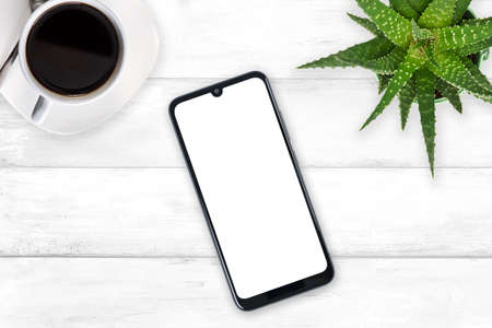 Top view of a new modern smartphone mockup with blank white screen on a wooden vintage table with coffee and green flower (copy space)