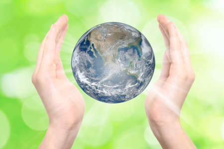 Female hands raised in a gesture of care for the Earth on a green eco background.