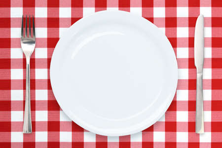 Italian cooking template - top view of an empty white plate and cutlery on a red checked tablecloth Stockfoto