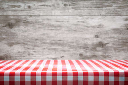 Italian cooking template - blank table with a red checked tablecloth on the blurred wooden vintage panels background.