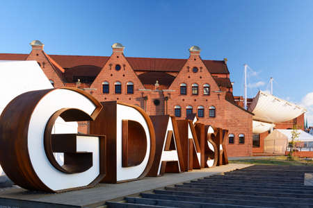 Gdansk, Poland - June 26, 2018: Gdansk city sign in the Old Town of the city on the background of Baltic Philharmonic