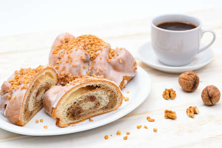 Tasty traditional polish croissants  - Croissant of Saint Martin (Rogal Świętomarciński) with white poppy seeds, nuts and cup of coffee.