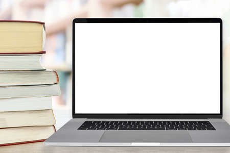Template for online education - stocks of books next to the laptop with a blank white screen on a desk