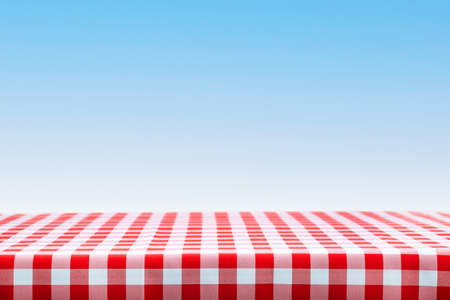 Italian cooking template - blank table with a red checked tablecloth on a blue sky background with copy space.