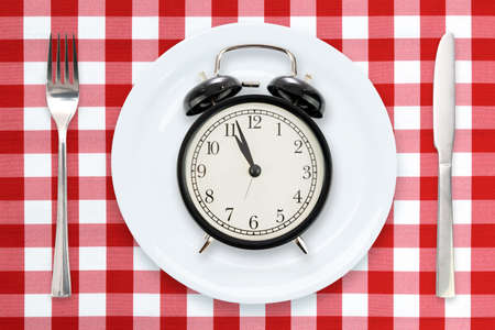 Time to Eating or Intermittent fasting concept - flat lay composition with alarm clock, plate and utensils on a red checked tablecloth. Stockfoto