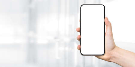 Woman hand holding a modern frameless smartphone with blank white screen on a blurred background of a modern corporate interior with copy space