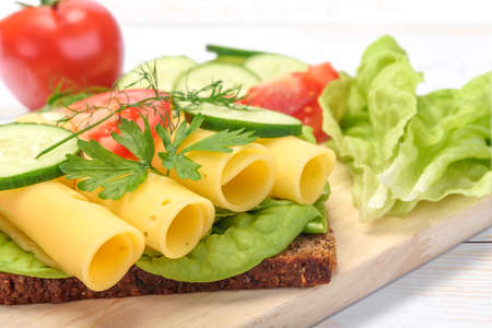Healthy eating concept - fresh and multi colored sandwich with dark wholemeal bread and cheese, lettuce, tomato, cucumber, dill, young onion on wooden board in close-up