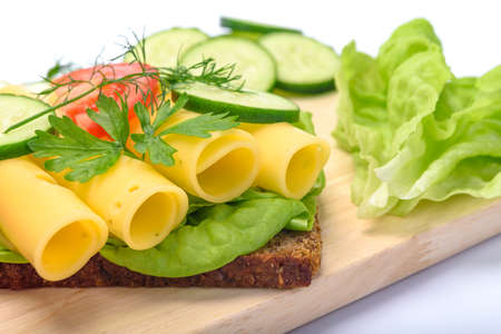 Making healthy eating concept - fresh and multi colored sandwich with dark wholemeal bread and cheese, lettuce, tomato, cucumber, dill, young onion on wooden board in close-up