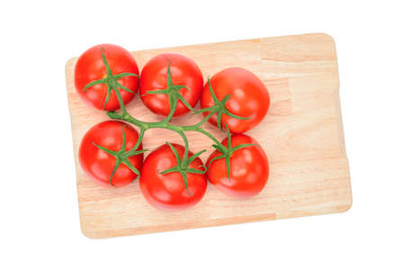 Top view of a fresh tomatoes bunch on a wooden cutting board. Stockfoto