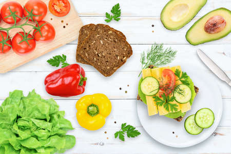 Flat lay top view of healthy and energetic breakfast - dark bread, tomatoes, avocado, peppers, cucumber and vegetable sandwich with cheese on a wooden vintage table.