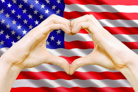 Composite image of American Patriotic love symbol - female hands makes heart sign on the background of the USA flag.
