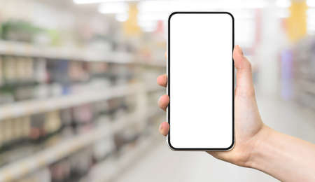 Shopping template or banner - woman hand holding a modern frameless smartphone with blank white screen on a blurred background of a hypermarket interior with copy space.