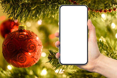 Christmas greetings or shopping template - woman hand holding modern frameless smartphone with blank white screen on blurred background of christmas tree and lighting decoration. Stockfoto
