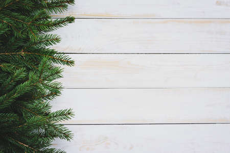 Christmas decoration concept - spruce branches on an old white wooden vintage table with copy space (reduced tones)