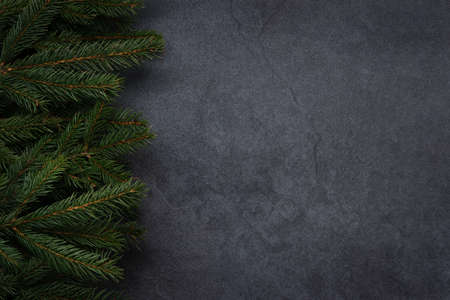Christmas decoration concept - spruce branches on a black vintage stone background with copy space.