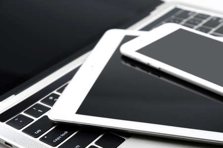 Collection of modern personal electronic devices: white smartphone, tablet and laptop in close-up