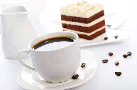 White cup of coffee with cocoa sponge cake on a saucer and scattered coffee beans in close-up Stock fotó - 164933114