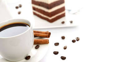 White cup of coffee with cinnamon sticks, cocoa sponge cake on a saucer and scattered coffee beans in close-up. Image with copy space for your advertisement text. Stock fotó