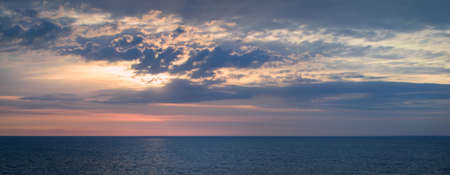 Panoramic view of a picturesque and dramatic sunrise sky over a vast and calm ocean. Standard-Bild