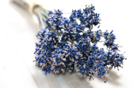 Bouquet of dried lavender flowers tied with a burlap twine on a wooden table in close-up Standard-Bild